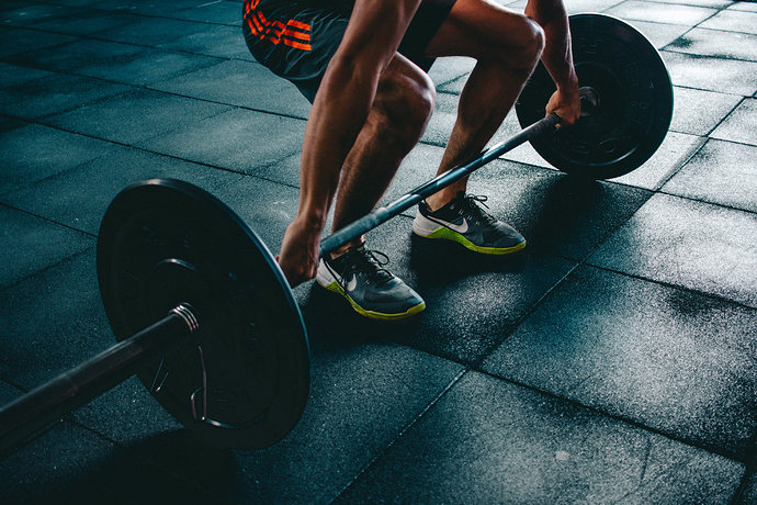 person-holding-barbell-841130