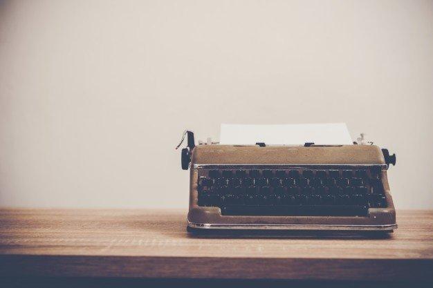 vintage-typewriter-wooden-table_1150-1807